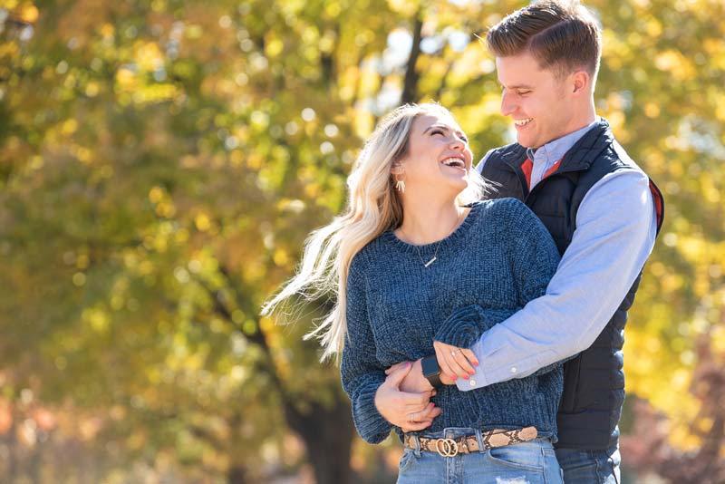 golden leaves in background of engagement photo