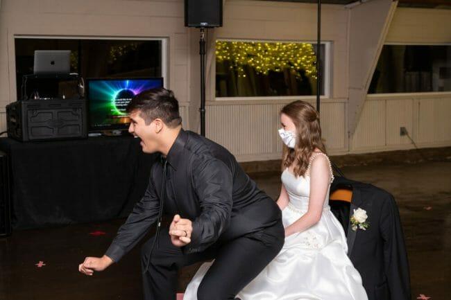 groom dancing on bride before garter