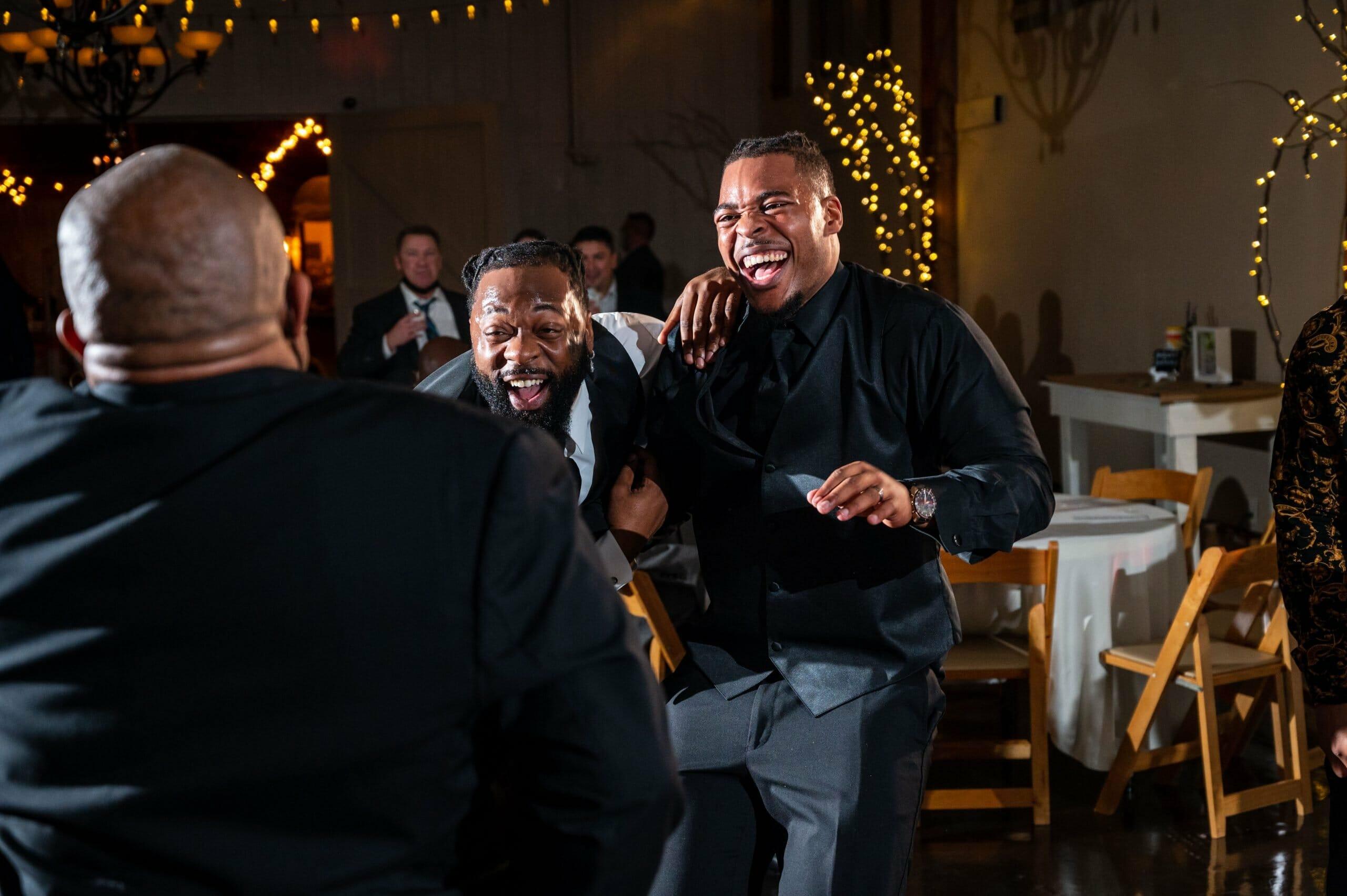 guys laughing at wedding