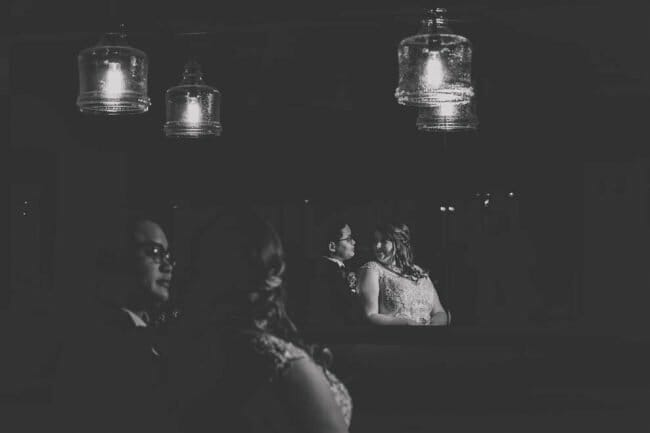 dramatic black and white wedding photo with couple reflection in mirror