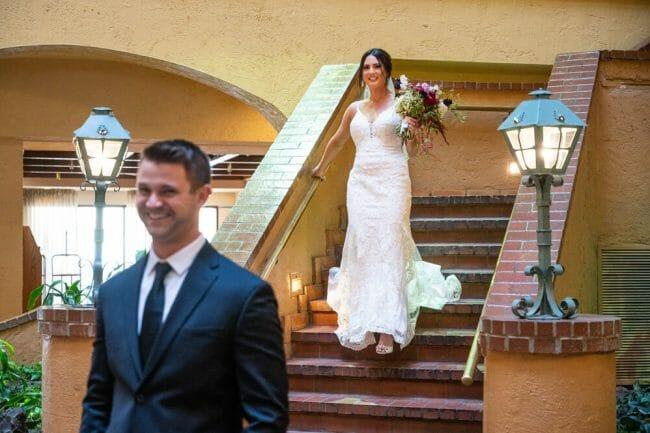 bride walking down stairs toward groom